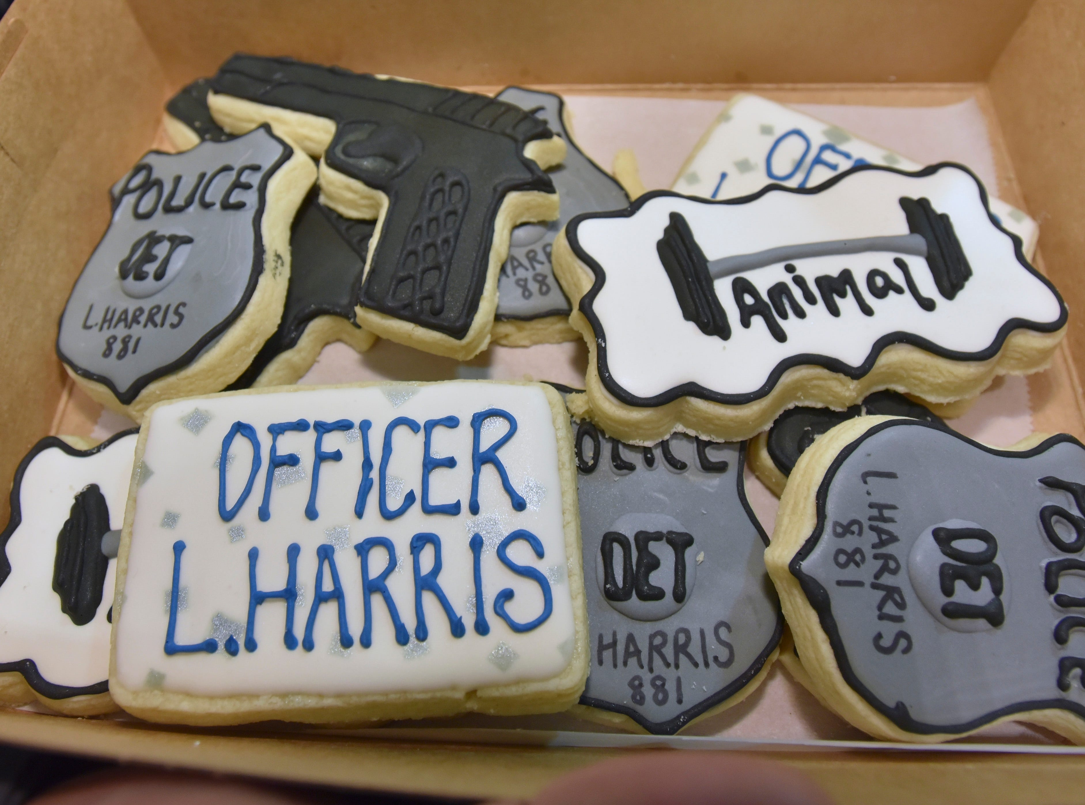 Family members and friends show off specially-made cookies for newly sworn officer Lamar Harris.