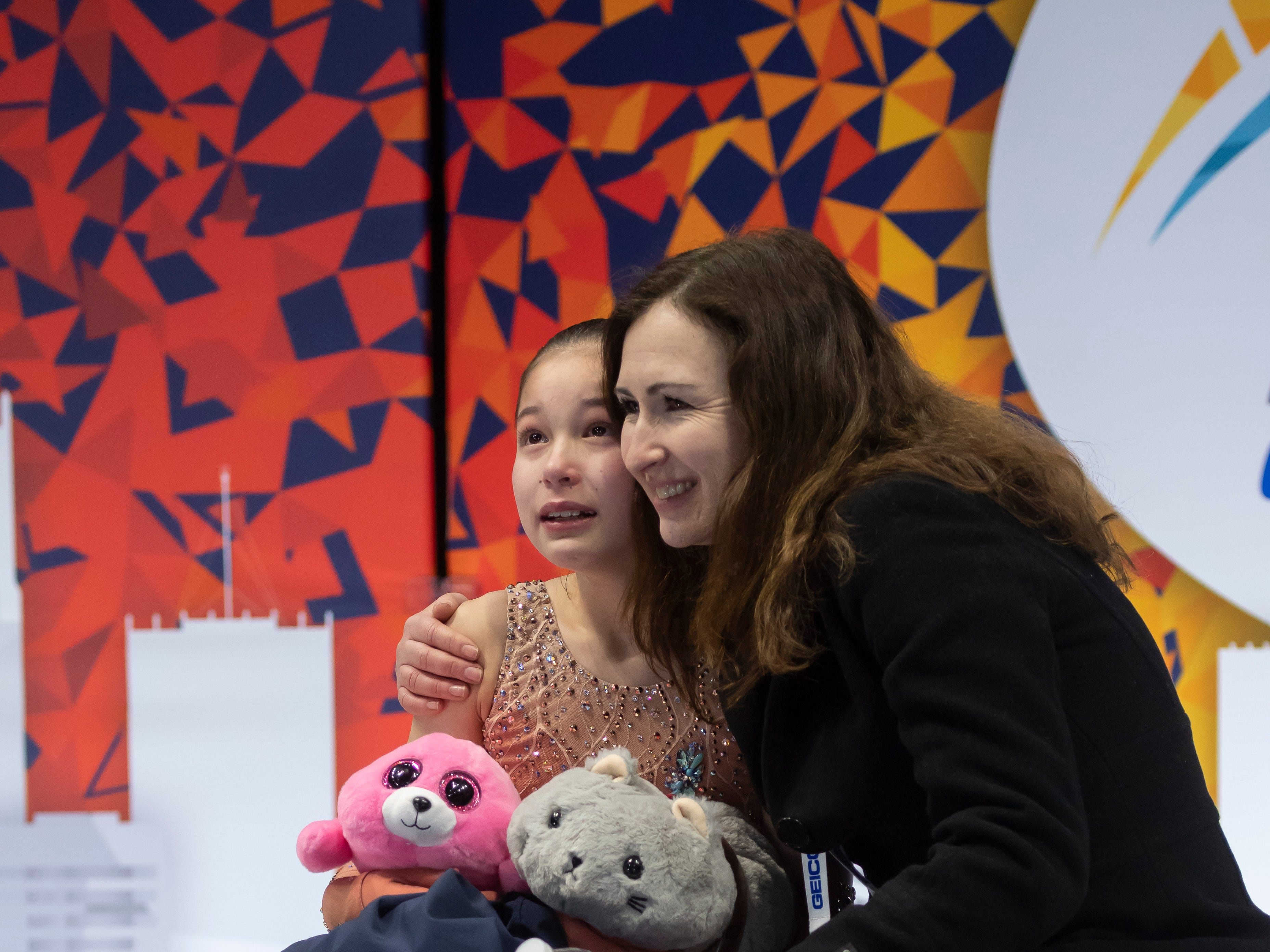 Thirteen-year-old Alysa Liu sits with her coach Laura Lipetsky while waiting for her score from the ladies short program.