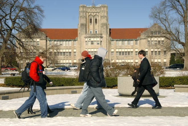 Students walk to class past the Olmsted Administration Hall on The University of Evansville campus.