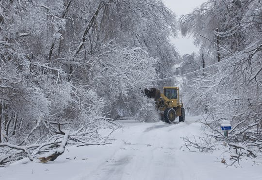 County worker Jerry Emmons uses an end loader to knock snow and ice from low-hanging branches along Yankeetown Road Wednesday morning. Emmons also cleared many fallen branches and collected snow from the roadway.