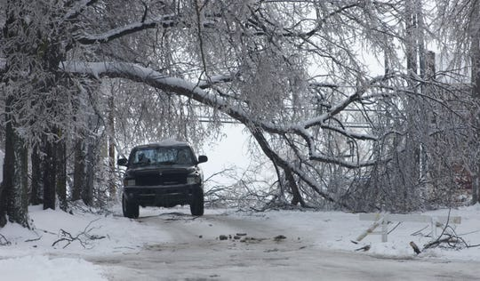 A massive tree limb creates a tunnel for motorists to navigate on Old State Road in Newburgh, Ind., Wednesday afternoon.