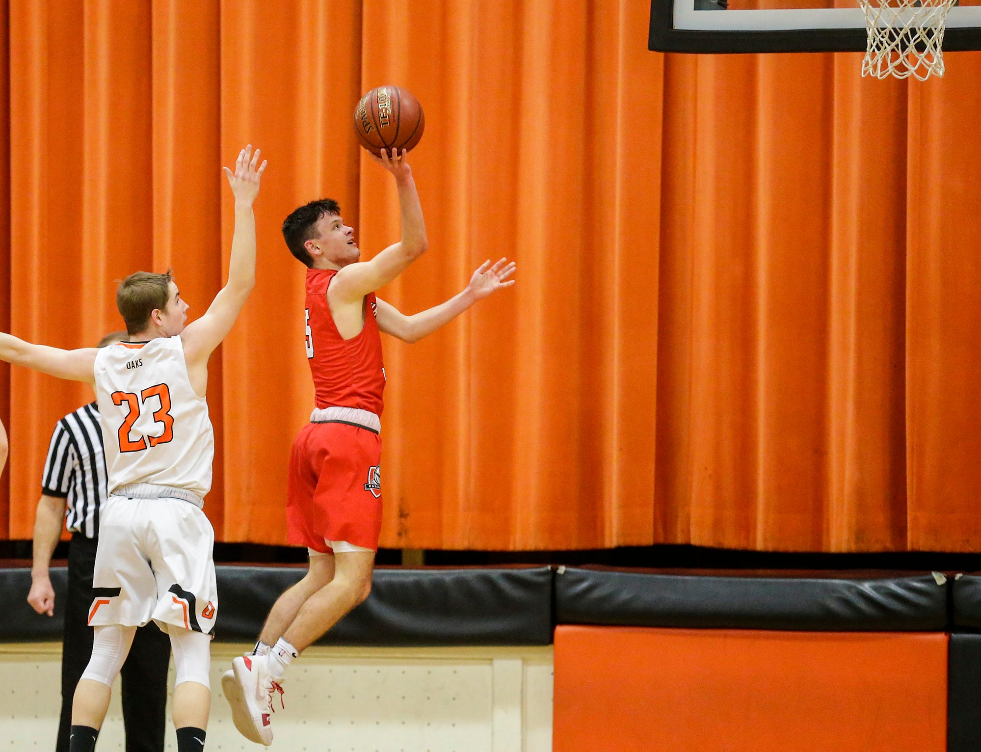 Oshkosh Lourdes Academy boys basketball's Jack McKellips goes up for a basket against Oakfield High School's Max Margelofsky during their game Thursday, January 24, 2019 in Oakfield. Lourdes Academy won the game 83-48. Doug Raflik/USA TODAY NETWORK-Wisconsin