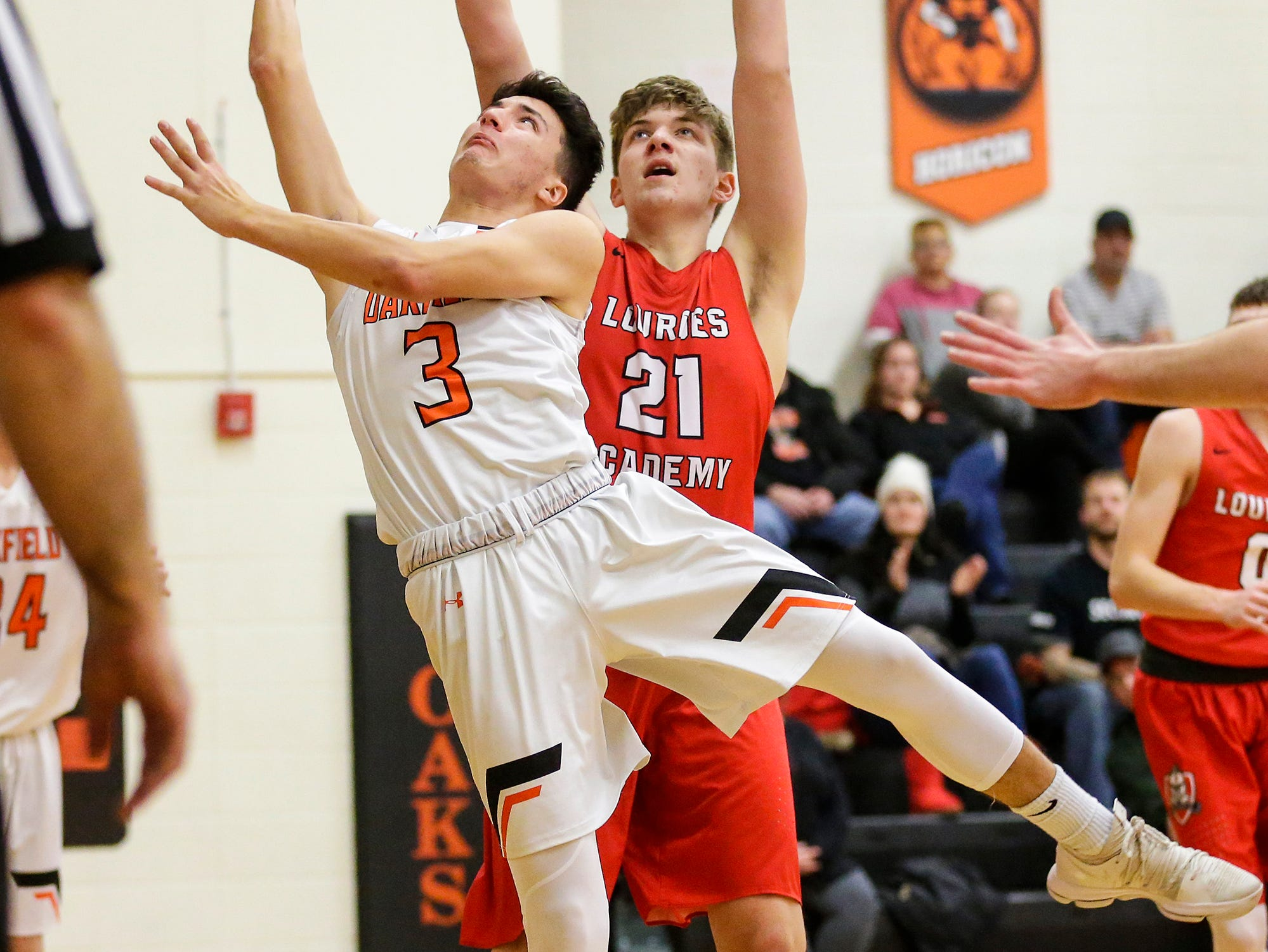 Oakfield High School boys basketball's Jacob Cedar gets fouled by Lourdes Academy's George Muench during their game Thursday, January 24, 2019 in Oakfield. Lourdes Academy won the game 83-48. Doug Raflik/USA TODAY NETWORK-Wisconsin