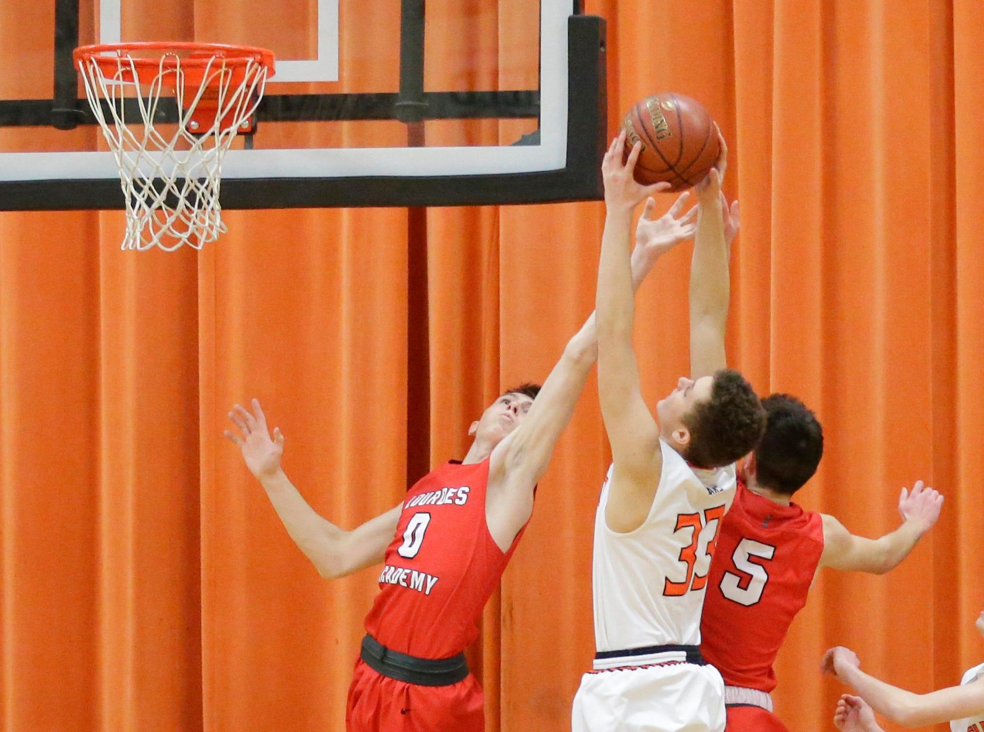 Oakfield High School boys basketball's Bart Bijl gets a rebound over Lourdes Academy's Hayden Jones (0) and Jack McKellips (5) during their game Thursday, January 24, 2019 in Oakfield. Lourdes Academy won the game 83-48. Doug Raflik/USA TODAY NETWORK-Wisconsin