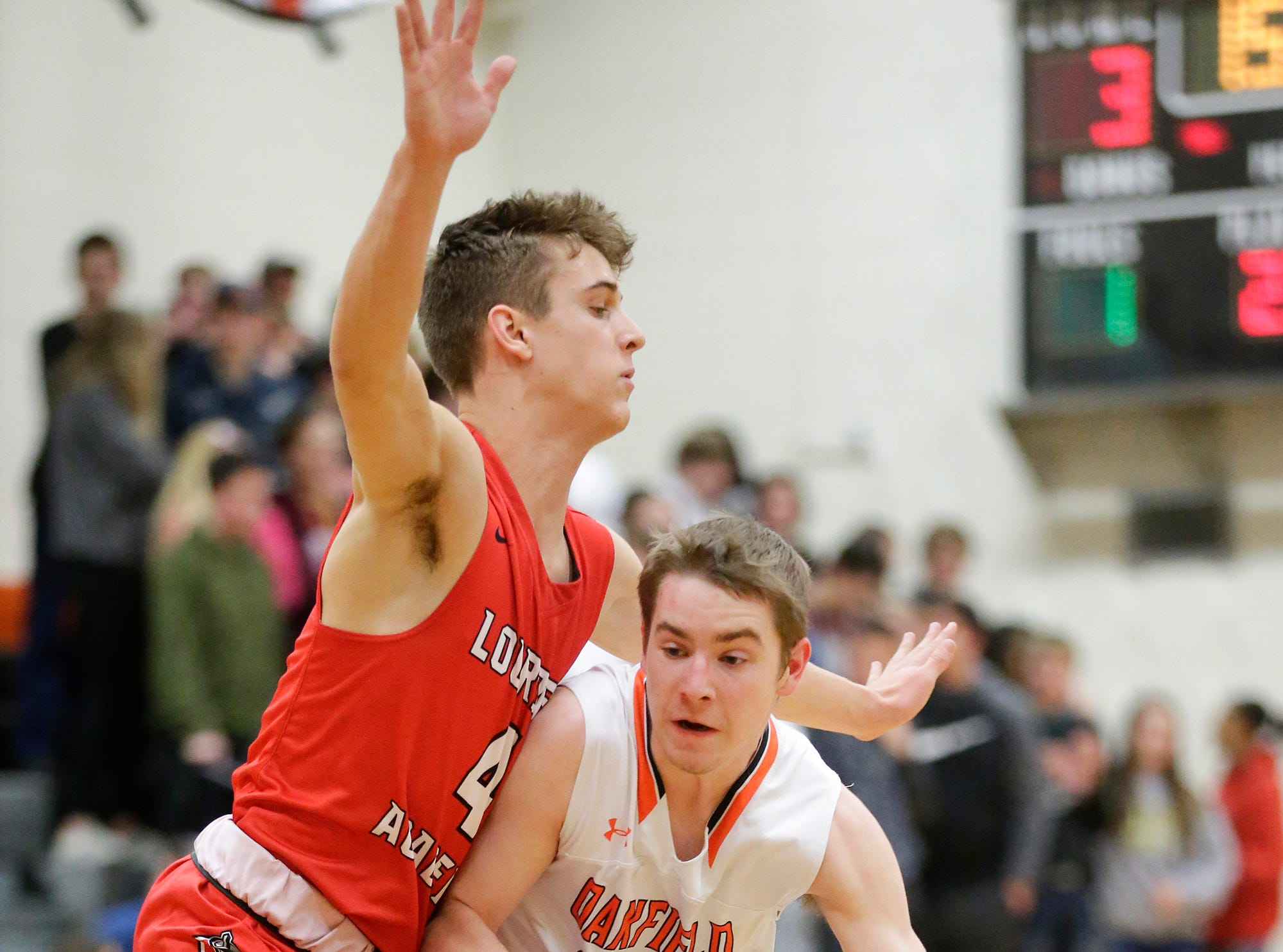Oakfield High School boys basketball's Max Margelofsky works his way towards the basket against Lourdes Academy's Preston Ruedinger during their game Thursday, January 24, 2019 in Oakfield. Lourdes Academy won the game 83-48. Doug Raflik/USA TODAY NETWORK-Wisconsin
