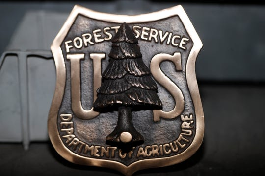 A door knocker made for the U.S. Forest Service is shown at Western Heritage Co. on Thursday, Jan. 24, 2019, in Loveland, Colo. Lynch saw online orders collapse almost immediately after the government shut down Dec. 22. The company sells buckles, keychains, commemorative coins and badges to employees of the Fish and Wildlife Service, the Forest Service, the Bureau of Land Management and other agencies. It also sells patches and some clothing. (AP Photo/David Zalubowski)