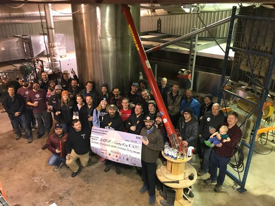 Northern Colorado breweries present a check for California fire relief on Thursday at Troubador Malting.