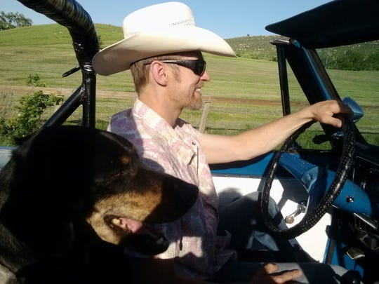Justin Larson driving with his dog, Mason.