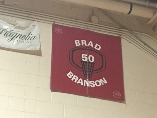 A banner hangs in the auxiliary gym at North Fort Myers High School commemorating 1976 Red Knights graduate Brad Branson, who wore No. 50 and later played a season and a half in the NBA and a dozen in Europe.