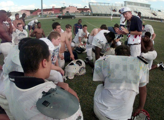 Estero High School football head coach Joe Hampton, right adresses his team at the end of practice in 1998.