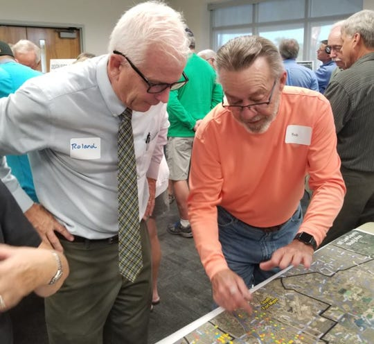 Roland Ottolini, executive director of Lee County's Natural Resources division speaks with resident Bob Clements about studies that have identified areas where flooding problems happened during Hurricane Irma. It was the first of three public sessions on county findings to date and the start of planning for long range improvements.