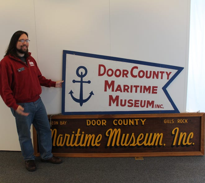 Door County Maritime Museum Curator Rhys Kuzdas with two of the museum's early signs; the one on top originally hung over the entrance to  the Gills Rock location. The signs will part of the exhibit celebrating the museum's 50th anniversary, opening Feb. 4.