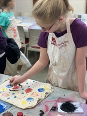 A young girl block prints a design on a tote bag, one of three types of printing visitors can try at Peninsula School of Art's Winter Print Event on Feb. 2.