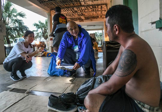 J.P. Torres Success Academy Principal Dexter Fullo, center, interviews Keison Andon, 28, outside the former fire department in Dededo during the Guam Homeless Coalition Point-In-Time Count conducted on Friday, Jan. 25, 2019.