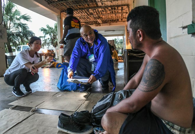 J.P. Torres Success Academy Principal Dexter Fullo, center, interviews Keison Andon, 28, outside the former fire department in Dededo during the Guam Homeless Coalition Point-In-Time Count in this Jan. 25, 2019, file photo.