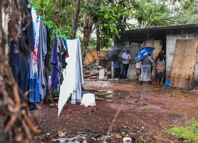 Department of Education officials brave an early morning rain shower as they interview a family living in an abandoned building in Dededo during the Guam Homeless Coalition Point-In-Time Count in this Jan. 25 file photo.