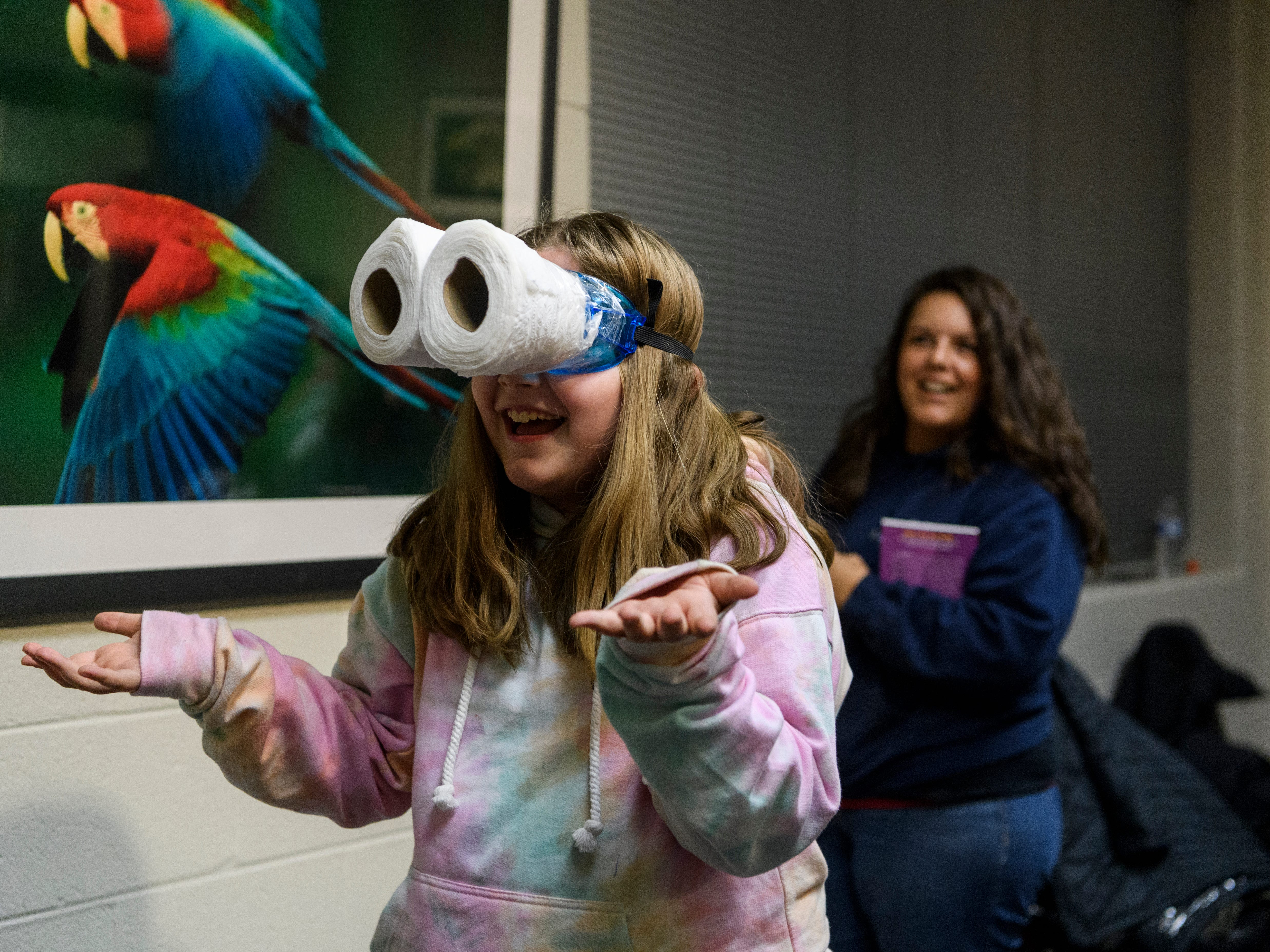 """Yazmin Oglesby, 10, a Cairo Elementary school student, laughs as she navigates """"owl vision googles"""" during a Family Night at the Henderson Community College's Preston Arts Center in Henderson, Ky., Thursday, Jan. 24, 2019. The event centered around a new National Geographic Photo Ark exhibit by photographer Joel Sartore, which will be on display for the public until March 15"""