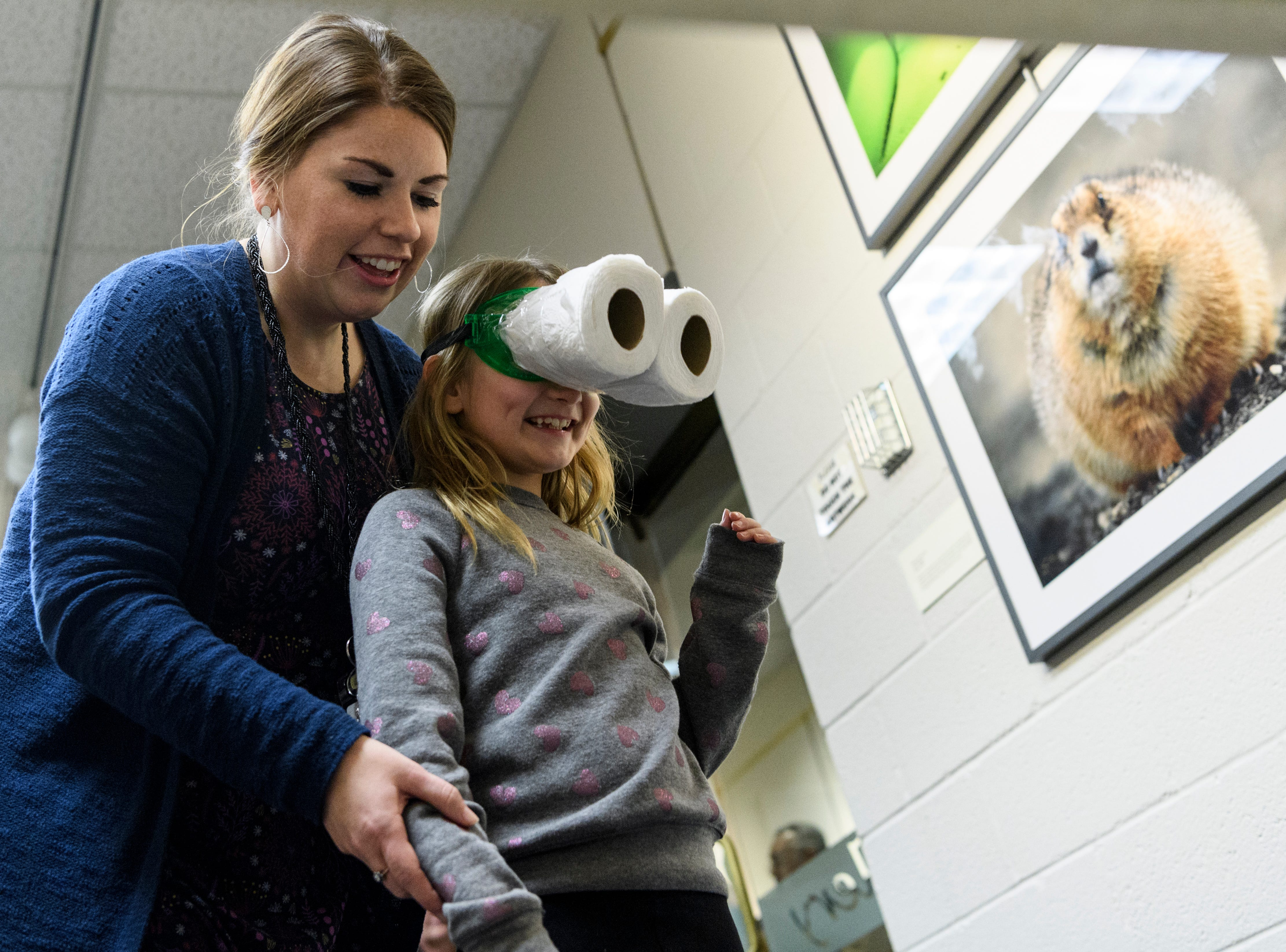 """Cairo Elementary school teacher Sarah Buckman helps second-grader Claire Stinson, 8, throw a clothespin into a plastic cup while wearing """"owl vision googles"""" during a nature education Family Night at Henderson Community College's Preston Arts Center in Henderson, Ky., Thursday, Jan. 24, 2019."""