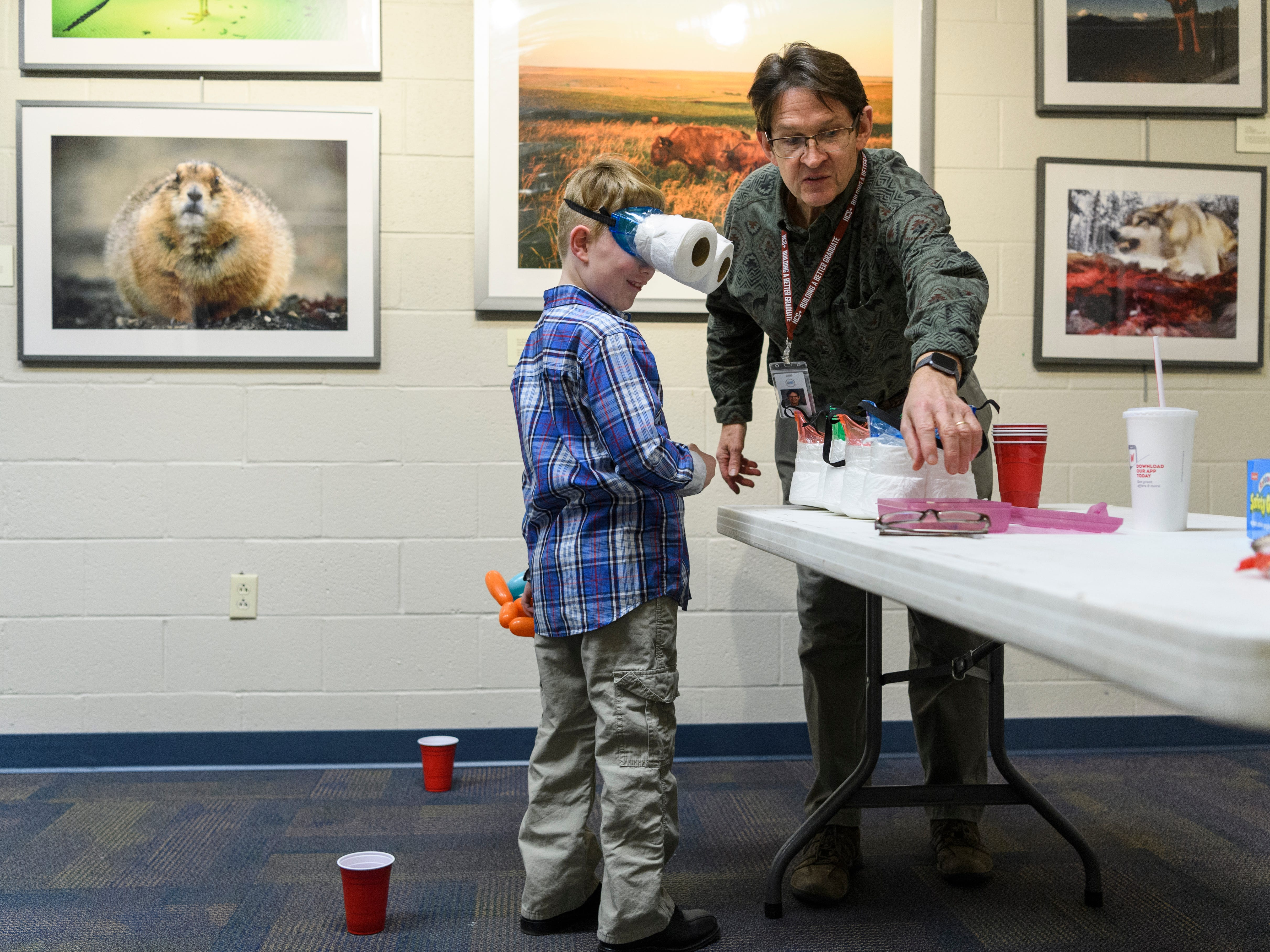 """Neil Jones, a Cairo Elementary school teacher, shows James Patterson, a Jefferson Elementary school student, how to look through """"owl vision googles"""" during a Family Night at the Henderson Community College's Preston Arts Center in Henderson, Ky., Thursday, Jan. 24, 2019. Cairo and Jefferson students and their families were invited to the event to see the National Geographic Photo Ark exhibit by photographer Joel Sartore, which will be on display for the public until March 15."""