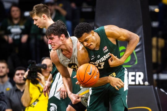 Iowa's Luka Garza, left, and Michigan State's Xavier Tillman tussle for a loose ball Thursday night. The Hawkeyes lost, 82-67.