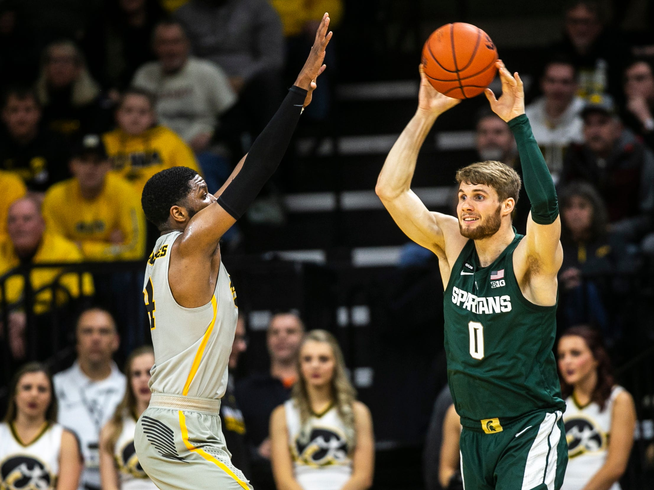 Iowa guard Isaiah Moss (4) defends Michigan State's Kyle Ahrens (0) during a NCAA Big Ten Conference men's basketball game on Thursday, Jan. 24, 2019, at Carver-Hawkeye Arena in Iowa City, Iowa.