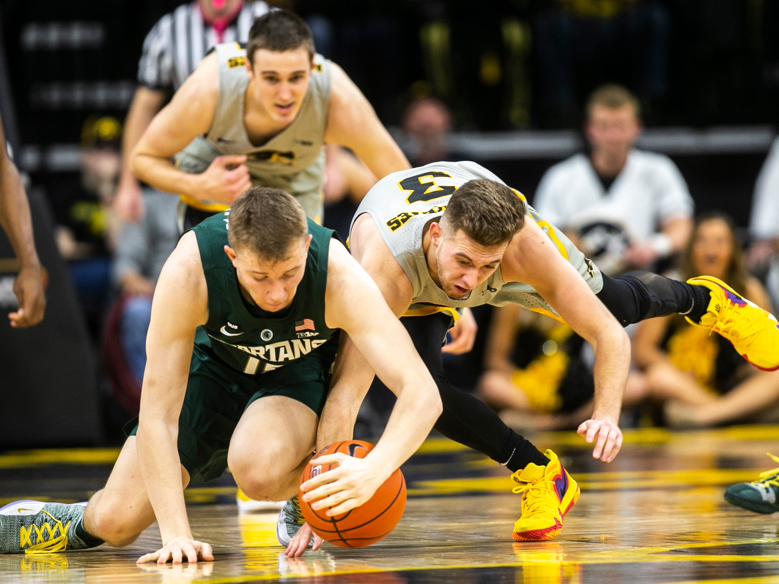 Iowa guard Jordan Bohannon (3) dives for a loose ball against Michigan State center Thomas Kithier (15) during a NCAA Big Ten Conference men's basketball game on Thursday, Jan. 24, 2019, at Carver-Hawkeye Arena in Iowa City, Iowa.
