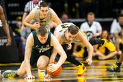 Iowa guard Jordan Bohannon (right) dives for a loose ball against Michigan State's Thomas Kithier in the first half Thursday. Bohannon came up with the ball, to the delight of the Carver-Hawkeye Arena crowd.