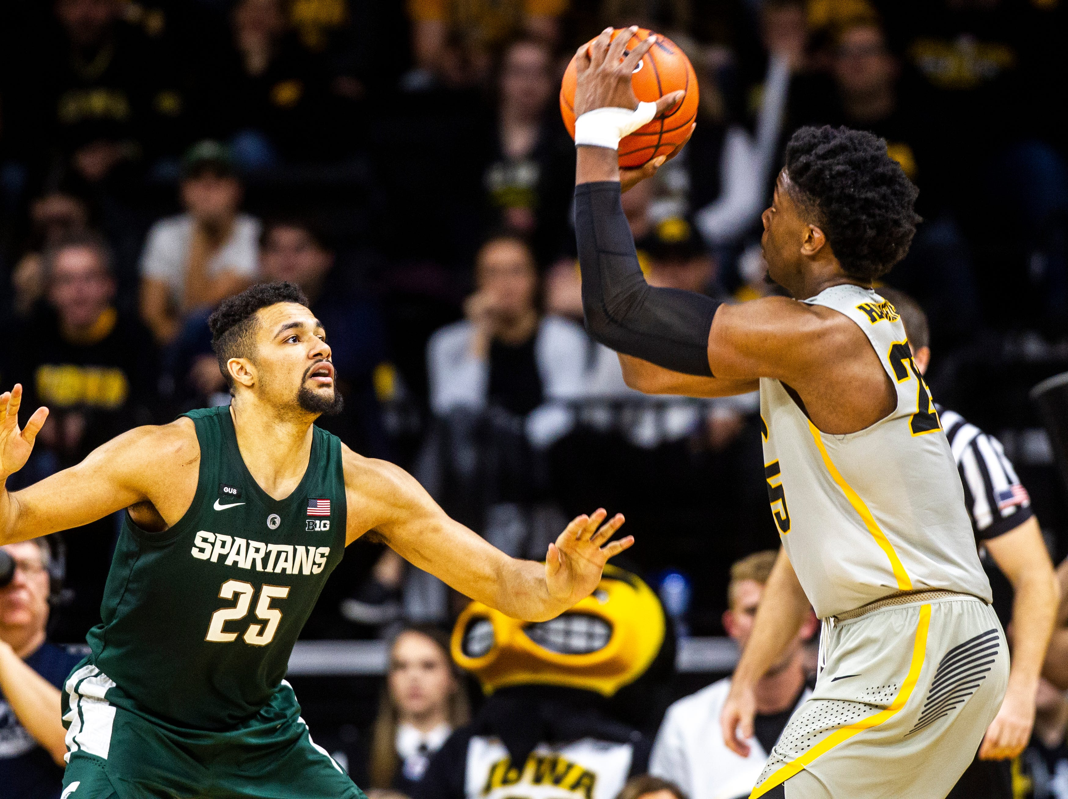 Iowa forward Tyler Cook (25) gets defended by Michigan State forward Kenny Goins (25) during a NCAA Big Ten Conference men's basketball game on Thursday, Jan. 24, 2019, at Carver-Hawkeye Arena in Iowa City, Iowa.