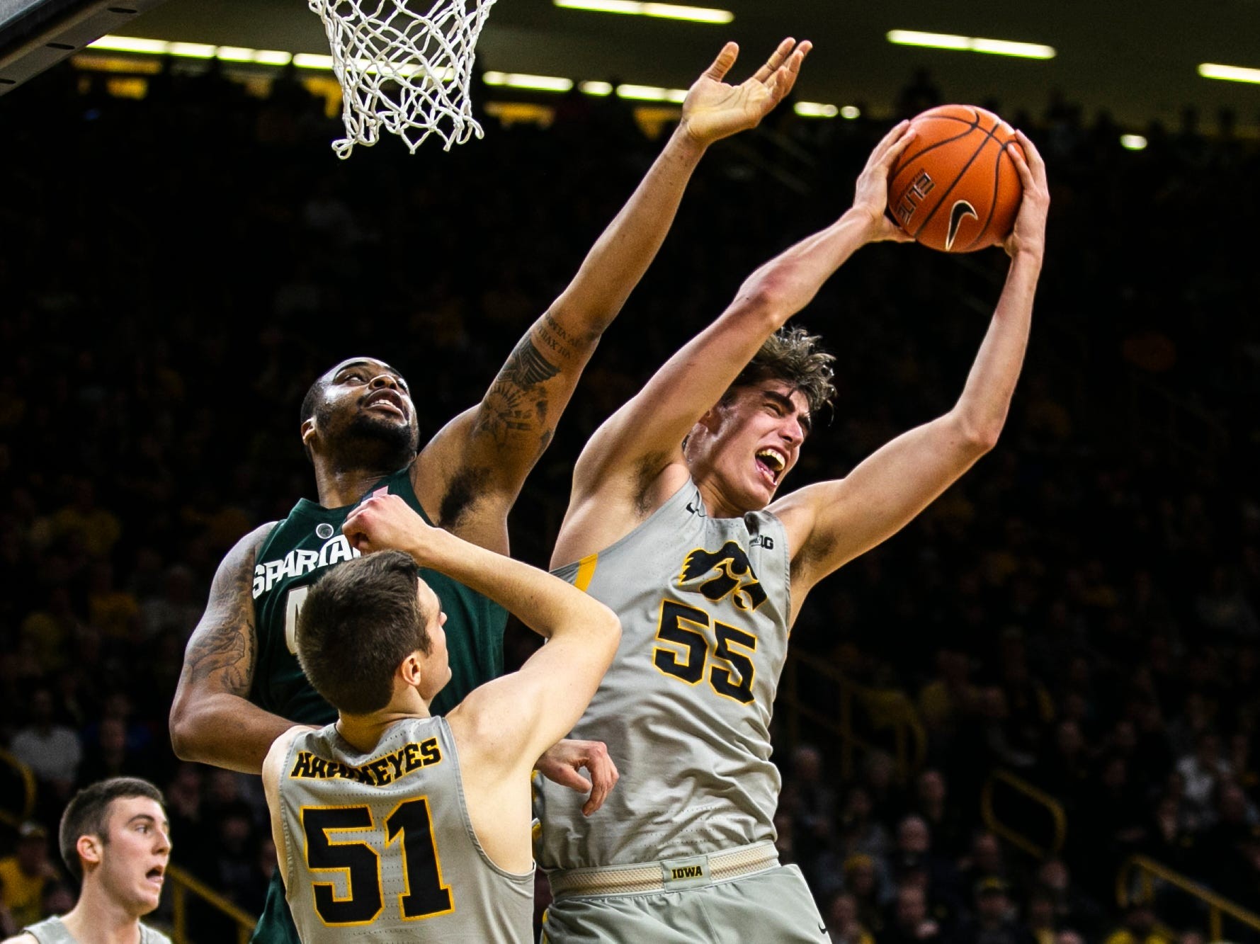 Iowa forward Luka Garza (55) pulls down a rebound during a NCAA Big Ten Conference men's basketball game on Thursday, Jan. 24, 2019, at Carver-Hawkeye Arena in Iowa City, Iowa.