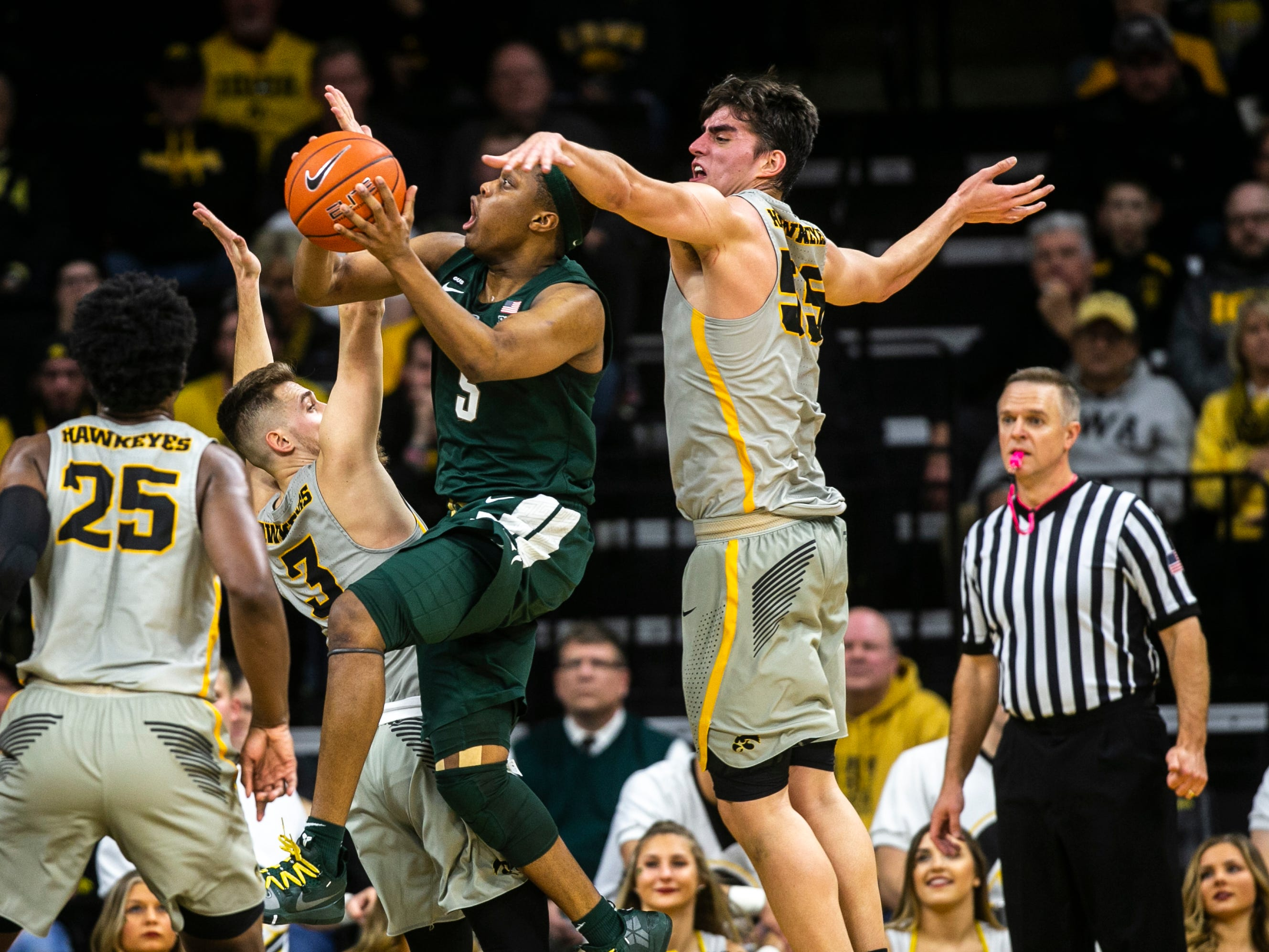 Iowa forward Luka Garza (55) defends Michigan State guard Cassius Winston on Thursday, Jan. 24, 2019, at Carver-Hawkeye Arena in Iowa City, Iowa.