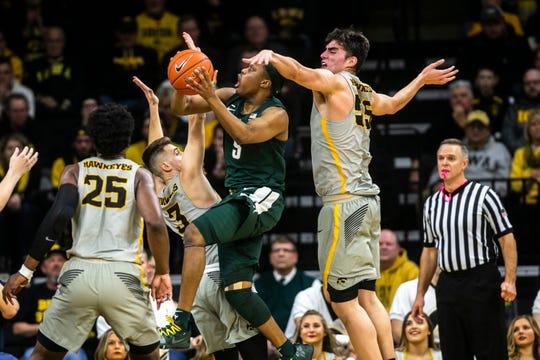 Iowa forward Luka Garza (55) defends Michigan State guard Cassius Winston on Thursday, Jan. 24, 2019, at Carver-Hawkeye Arena in Iowa City, Iowa.