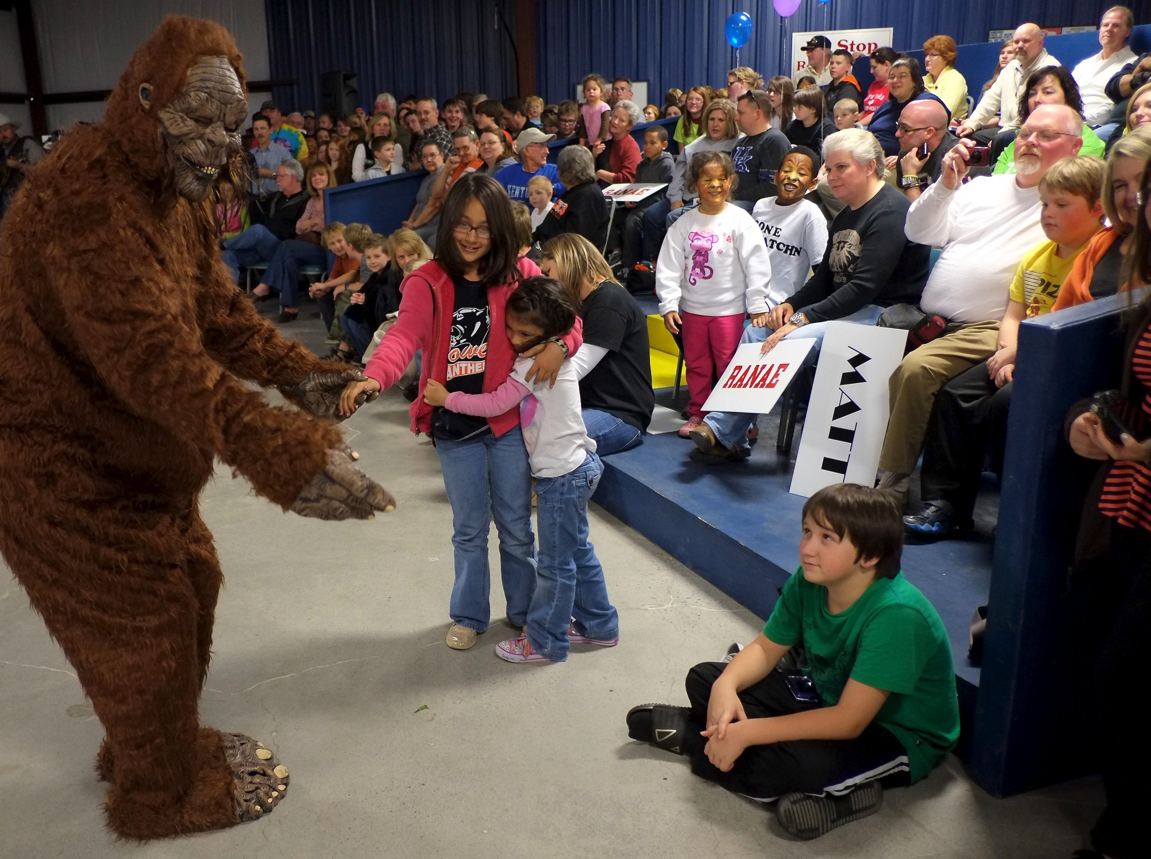 Bigfoot tries to dance with Sydney Chianelli, 9, center, and her sister Maddy Chianelli, 5, before for an appearance by the TV personalities from the Animal Planet's Finding Bigfoot show on Friday, November 16, 2012 at the Powell Auction House.
