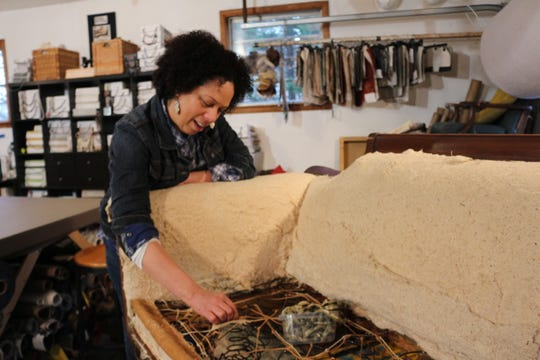 Rachel Fletcher points out the shoddy webbing inside a sofa she's currently working on.