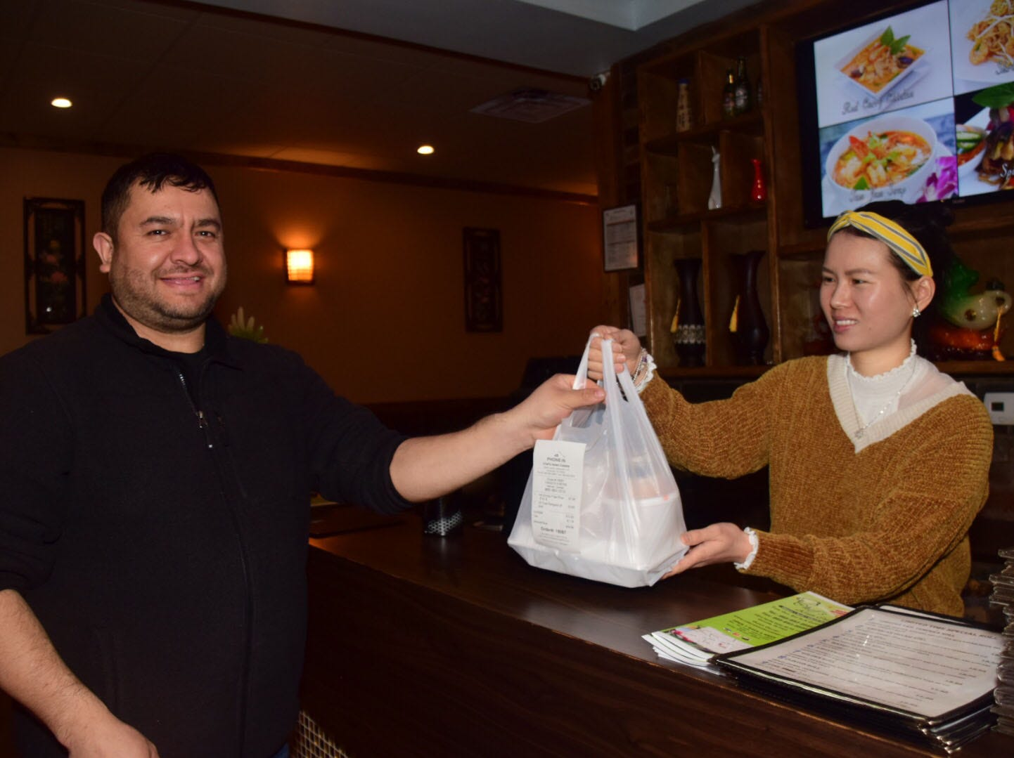 Elmer Perez picks up his lunch from co-owner Echo Liang at Chef's Asian Cuisine Thursday, Jan. 24.
