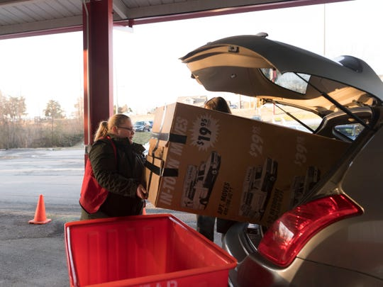Emily Deline helps unload a boxed Christmas tree being donated at the Karm Store in Farragut on Thursday, January 24, 2019.