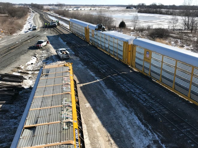 Norfolk Southern crews work on three of the four derailed train cars that jumped the track Thursday afternoon. The trucks of the fourth car broke off of the car in the derailment, based on observations from the scene. It remains on its side.