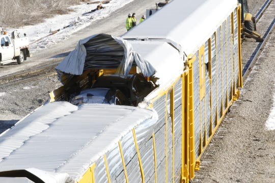 Two automobiles were visible late Friday morning inside one of the derailed train cars after it was put back onto the tracks.