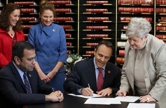 Gov. Matt Bevin, center, files paperwork to run for re-election with State sen. Ralph Alvarado, left, as his running mate. Director of Elections Mary Sue Helm, right, observes. The governor's wife, Glenna Bevin, and Alvarado's wife, Dawn Alvarado, far left, are also pictured.
