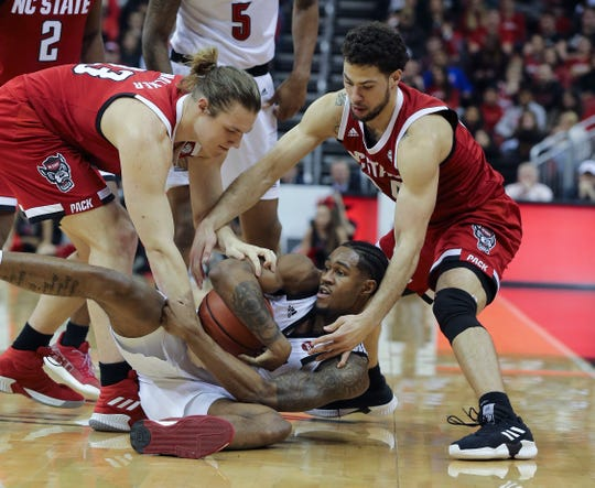 Louisville's V.J. King fights for the ball against two NC State players during a January game at the KFC Yum Center.