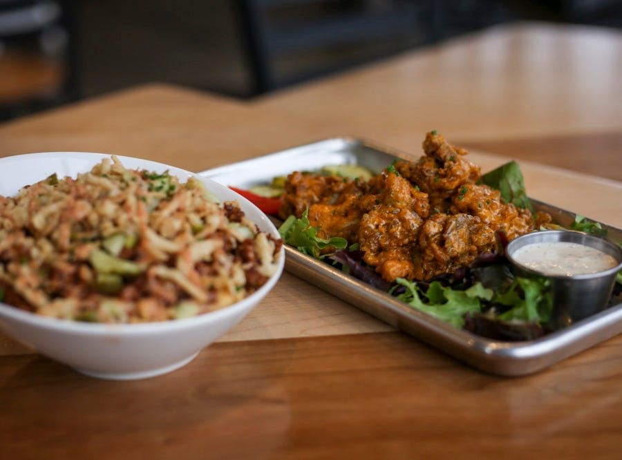 Left to right: Cheeseburger Mac with vegan sausage and crispy onions and Chicken Fried Mushroom Wings featuring oyster mushrooms that are marinated, fried and then tossed in buffalo sauce at V-Grits,  southern-style vegan comfort food, at 1025 Barret Ave in Louisville, Ky. on Thursday, January 24, 2019.