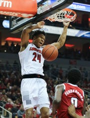 Louisville's Dwayne Sutton (24) dunked over NC State's D.J. Funderburk (0) during their game at the Yum Center. Jan. 24, 2019