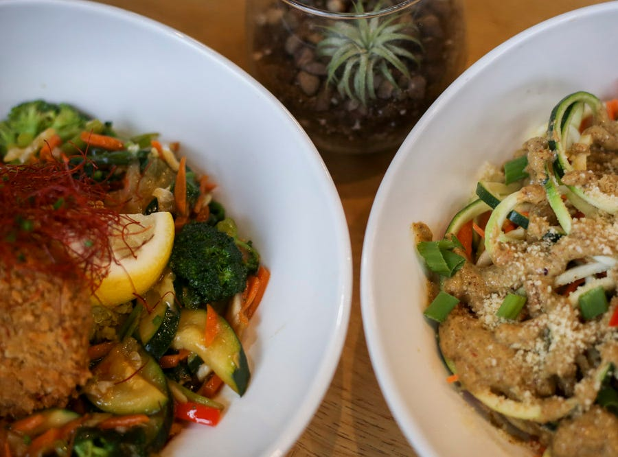 Left to Right: Citrus Crab Stir Fry, mixed vegetables in a citrus spiced tamarind glaze topped with a jack crab cake, and Raw Pad Thai, a chilled salad made with zucchini noodles and mixed vegetables topped with almond ginger Thai dressing, at V-Grits,  southern-style vegan comfort food, at 1025 Barret Ave in Louisville, Ky. on Thursday, January 24, 2019.