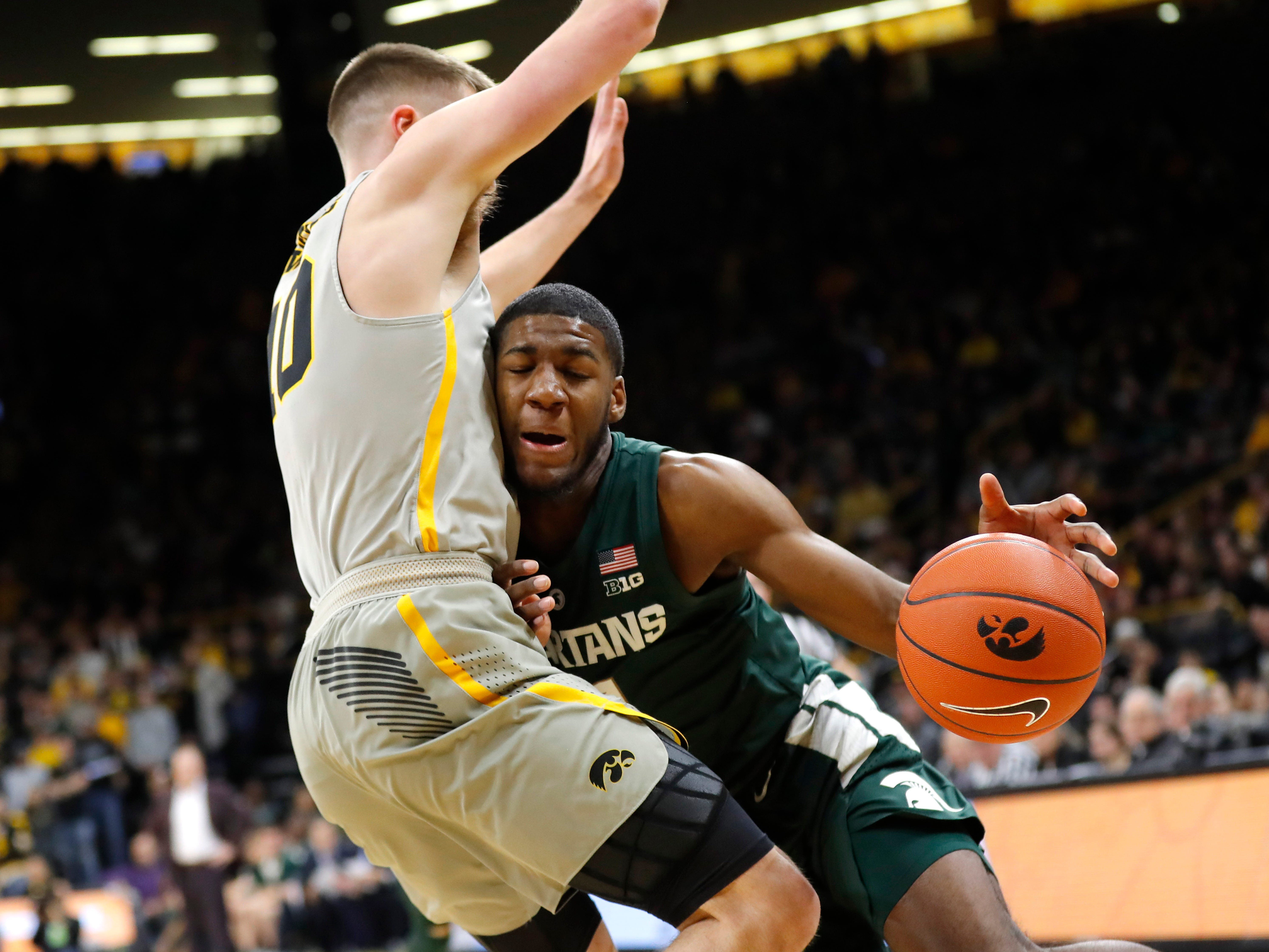 Michigan State forward Aaron Henry, right, tries to drive around Iowa guard Joe Wieskamp during the first half of an NCAA college basketball game Thursday, Jan. 24, 2019, in Iowa City, Iowa.