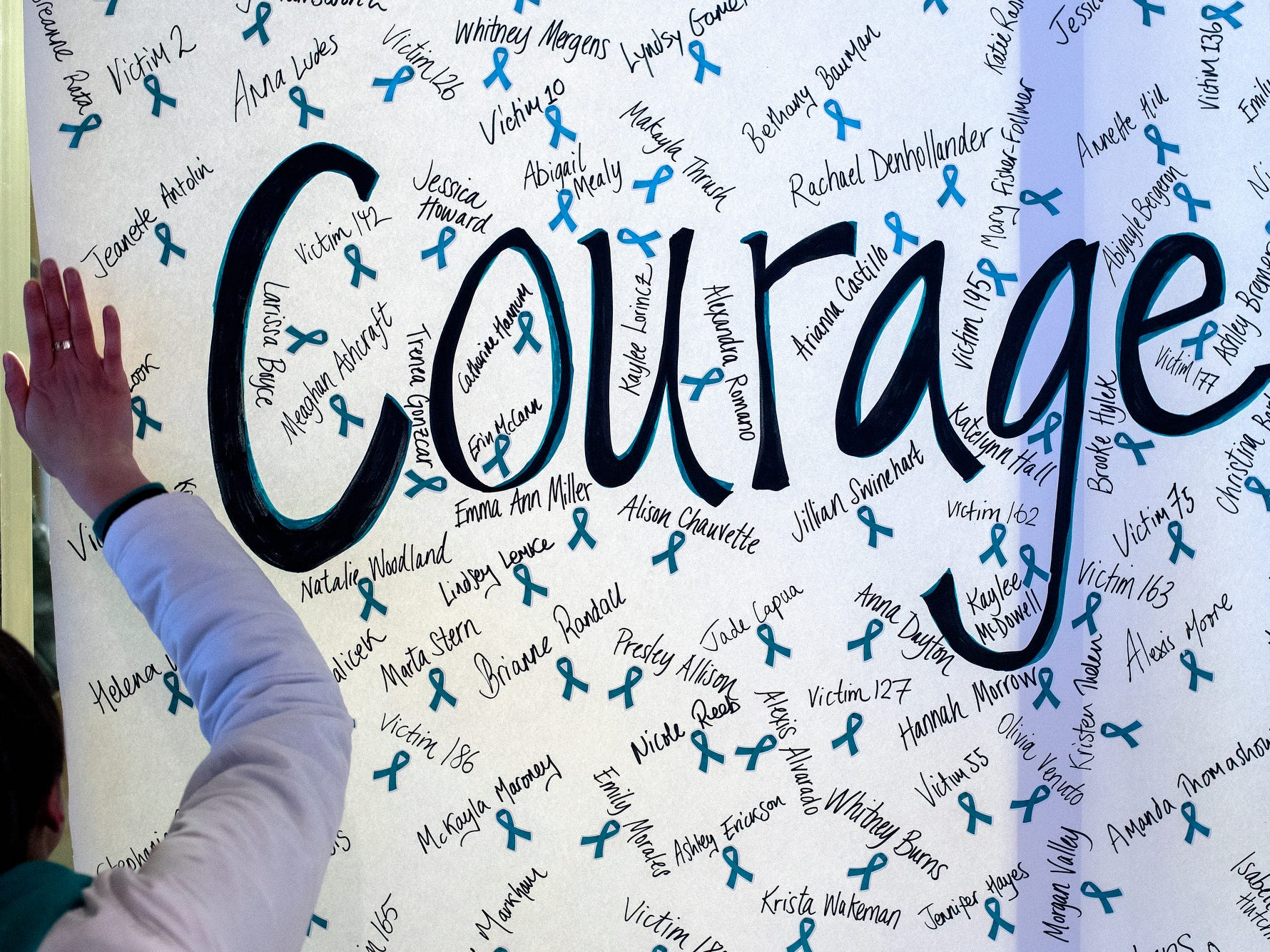 "A ReclaimMSU volunteer helps put up a sign reading 'courage' with the names of Nassar survivors during the ""One Year On: Celebrating Courage and Creating Change"" event on Thursday, Jan. 24, 2019, outside the Hannah Administration Building on the Michigan State University campus in East Lansing. The event was organized by Reclaim MSU and held on the one-year anniversary of Larry Nassar's sentencing."