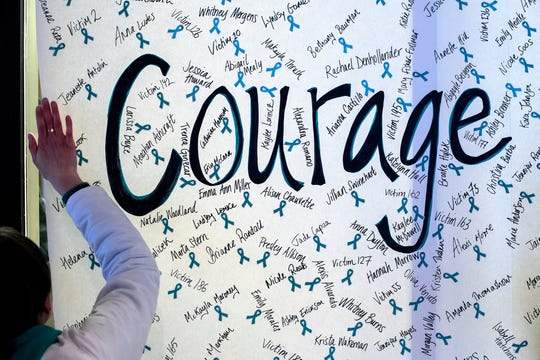 """A ReclaimMSU volunteer helps put up a sign reading 'courage' with the names of Nassar survivors during the """"One Year On: Celebrating Courage and Creating Change"""" event on Thursday, Jan. 24, 2019, outside the Hannah Administration Building on the Michigan State University campus in East Lansing. The event was organized by Reclaim MSU and held on the one-year anniversary of Larry Nassar's sentencing."""