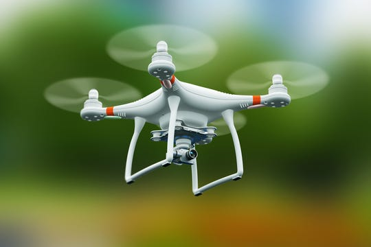 Creative abstract 3D render illustration of professional remote controlled wireless RC quadcopter drone with 4K video and photo camera for aerial photography flying in the air outdoors with selective focus effect