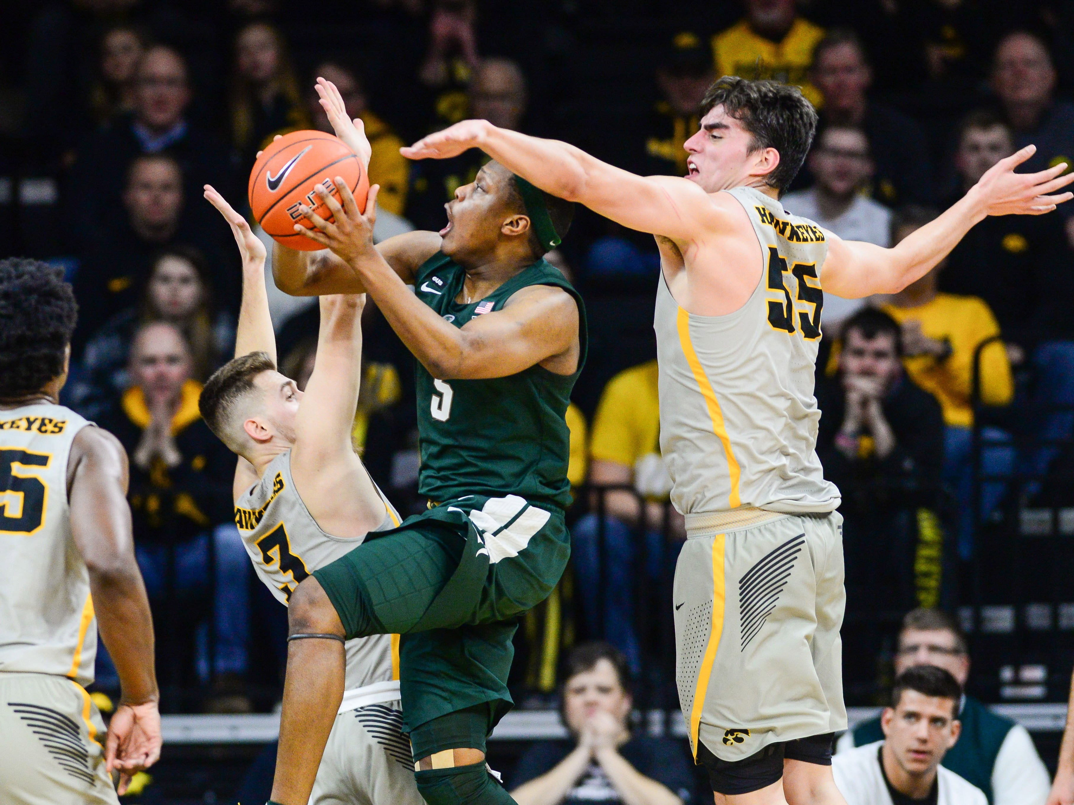 Iowa Hawkeyes forward Luka Garza (55) and guard Jordan Bohannon (3) and forward Tyler Cook (25) defend the shot by Michigan State Spartans guard Cassius Winston (5) during the first half at Carver-Hawkeye Arena.