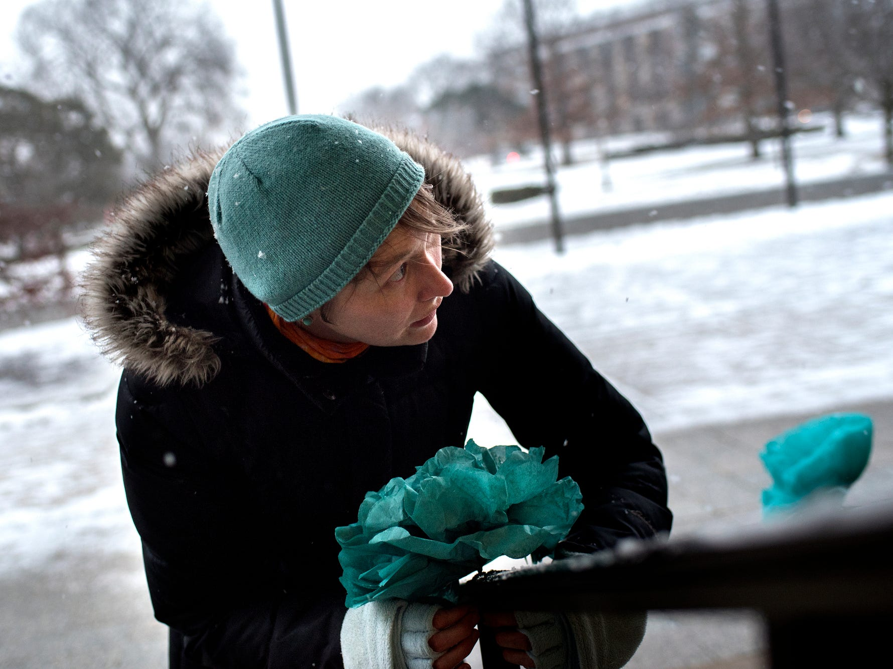 "Grad student and ReclaimMSU member Betsy Riley places teal paper flowers on the step rails before the ""One Year On: Celebrating Courage and Creating Change"" event on Thursday, Jan. 24, 2019, outside the Hannah Administration Building on the Michigan State University campus in East Lansing. The event was organized by Reclaim MSU and held on the one-year anniversary of Larry Nassar's sentencing."