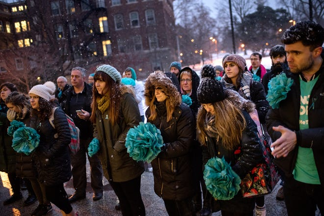 """Participants look on during the """"One Year On: Celebrating Courage and Creating Change"""" event on Thursday, Jan. 24, 2019, outside the Hannah Administration Building on the Michigan State University campus in East Lansing. The event was organized by Reclaim MSU and held on the one-year anniversary of Larry Nassar's sentencing."""