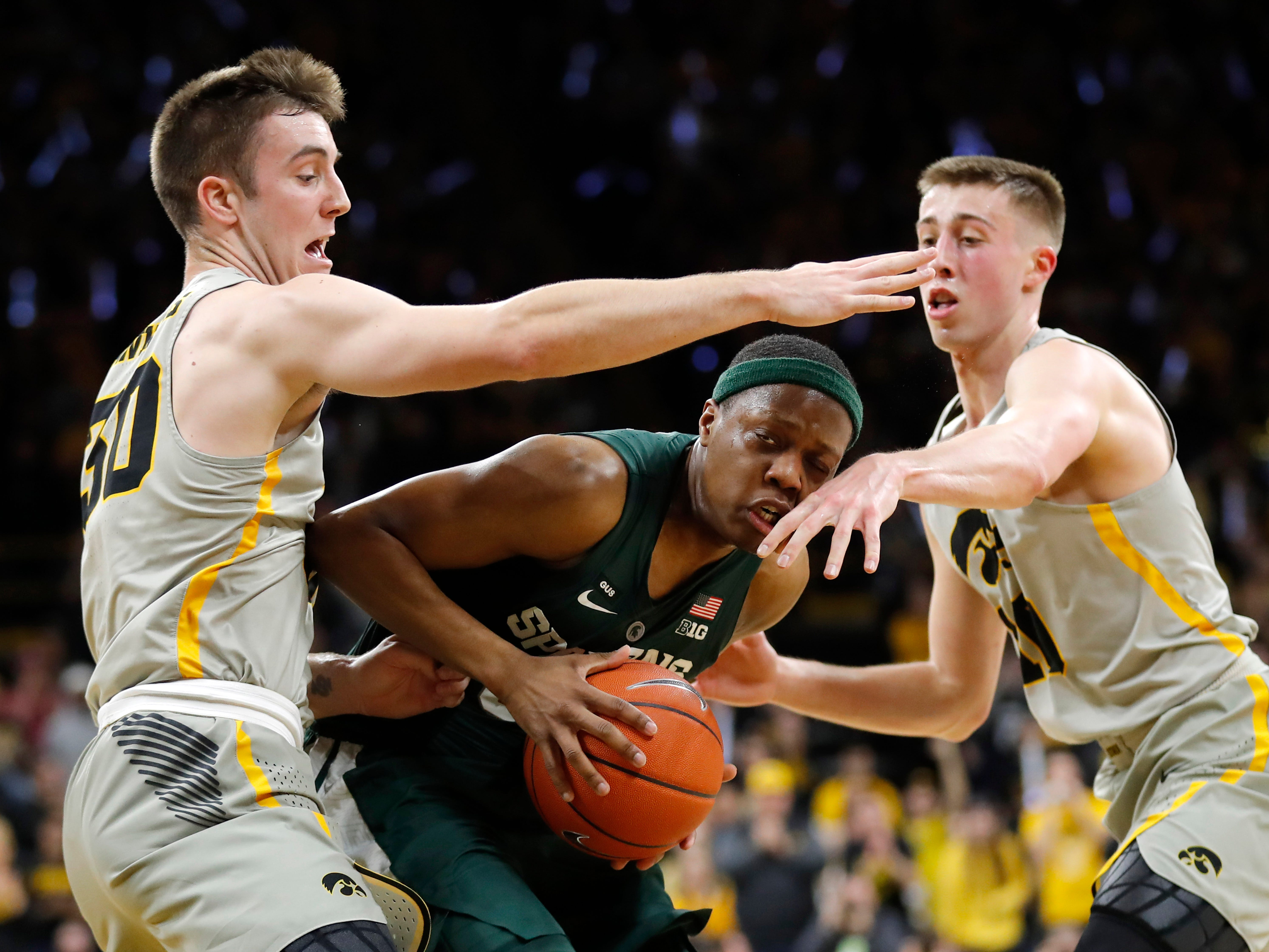 Michigan State guard Cassius Winston, center, drives between Iowa's Connor McCaffery, left, and Joe Wieskamp, right, during the first half of an NCAA college basketball game Thursday, Jan. 24, 2019, in Iowa City, Iowa.